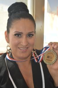 Lucy muestra su medalla, otorgada por City f Hope, por haber terminado en tratamiento de radiación. [Foto: Iliana Salguero]